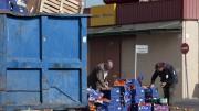 Gente recogiendo comida en la puerta de un supermercado