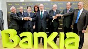 presidente del hasta ahora llamado Banco Financiero y de Ahorros, Rodrigo Rato (centro), posa junto a los presidentes de las seis entidades, que junto a Caja Madrid, conforman el grupo Bankia, ante el nuevo nombre comercial del grupo, escrito en color lima.